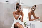 Young woman sitting in bathroom and applying facepack. Beautiful female in front of mirror applying facial mask.