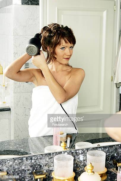 Young woman in bathroom, blow-drying her hair