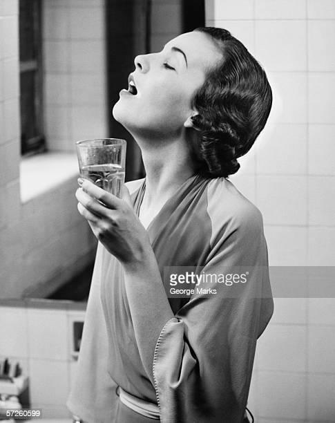 Jeune femme dans la salle de bains, Faire des gargarismes eau (B & W
