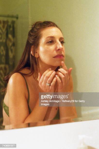 Young Woman In Bathroom Mirror