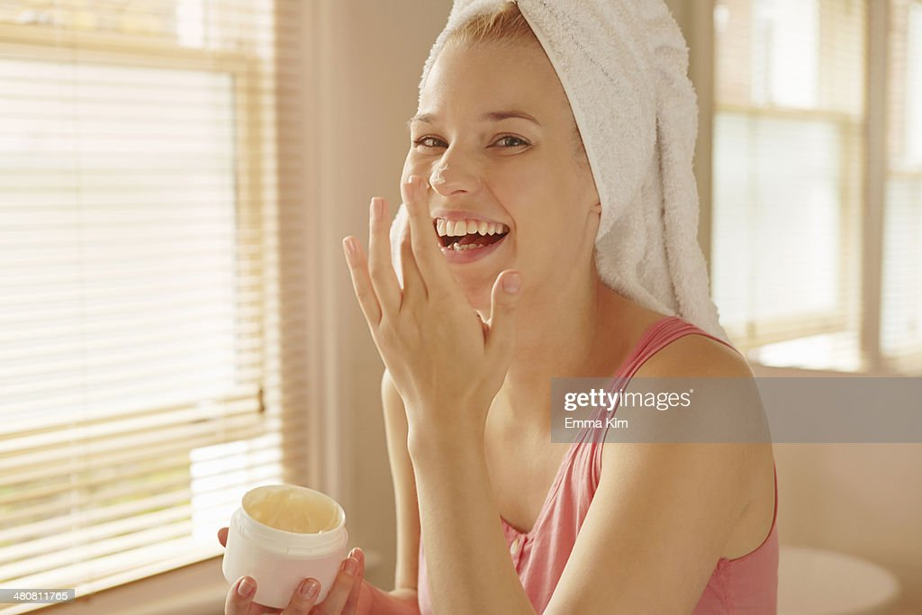 Young woman in bathroom putting on face cream