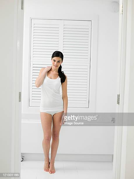 Young woman in bathroom with louvered door