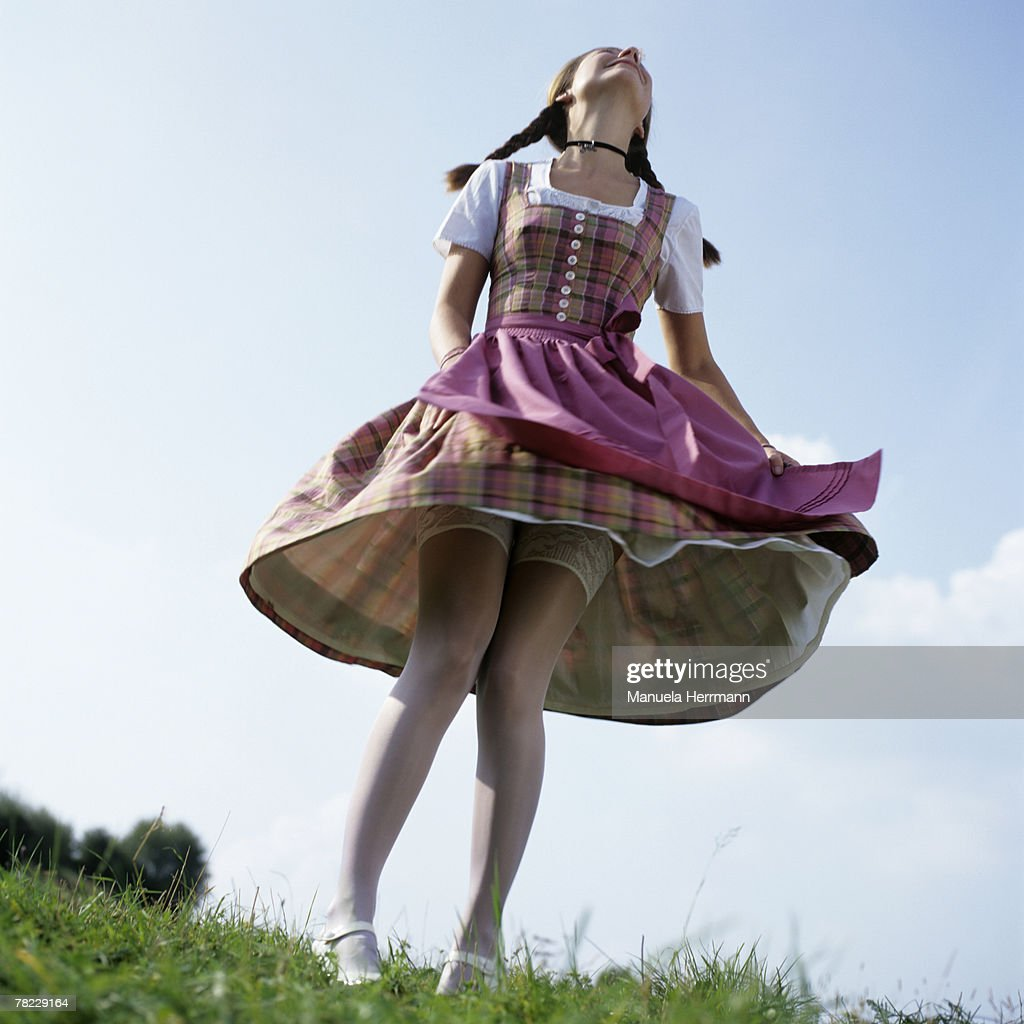 young woman in Bavarian dress dancing with lifted skirt
