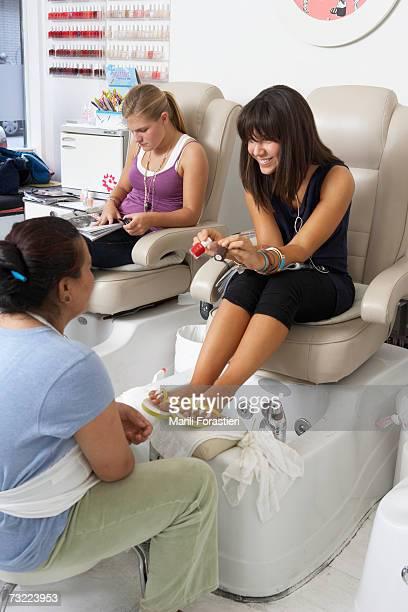 Young woman in beauty salon selecting nail polish
