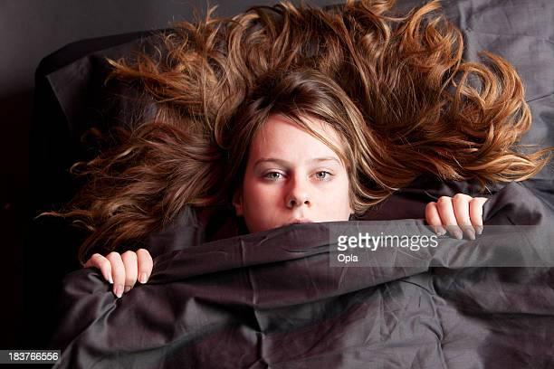 Jeune femme éveillée dans la chambre allongé