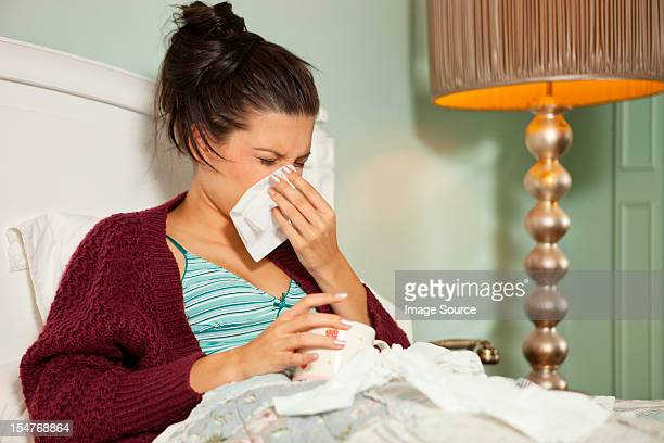Young woman in bed with cold