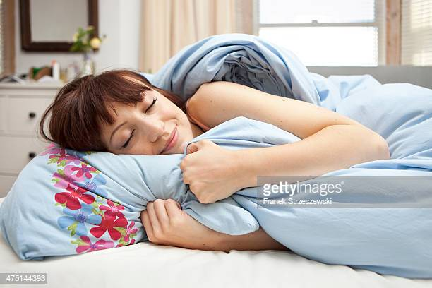 Young woman in bed with eyes closed