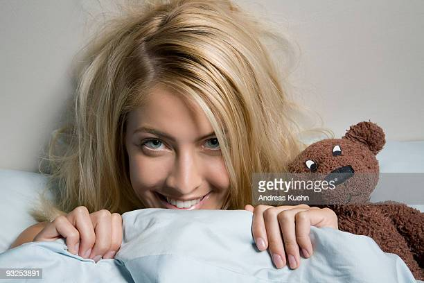 Young woman in bed with Teddy bear, close up.