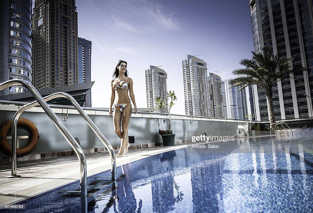 Young woman in bikini at rooftop swimming pool, Dubai, United Arab Emirates