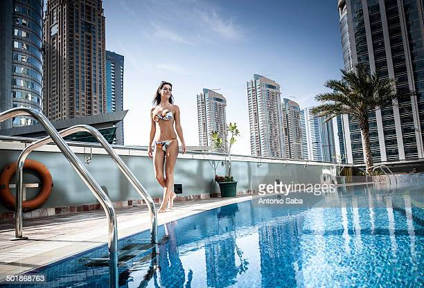 Young woman in bikini at rooftop swimming pool, Dubai, United Arab Emirates