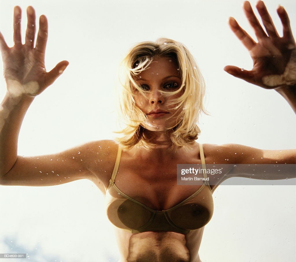 Young woman in bikini crawling on glass, portrait, view from below