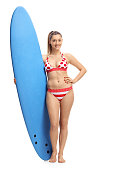 Full length portrait of a young woman in bikini holding a surfboard isolated on white background