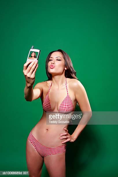 Young woman in bikini, photographing self with mobile phone