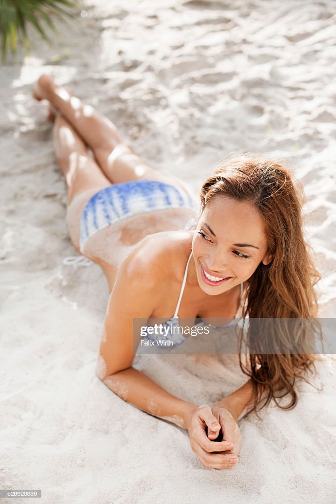 Young woman in bikini resting on beach : Photo