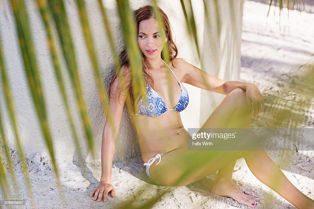 Young woman in bikini resting on beach : Photo