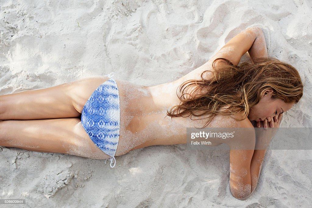 Young woman in bikini resting on beach : ストックフォト