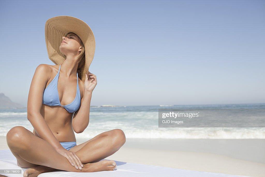 Young woman in bikini sitting at beach : Stock Photo