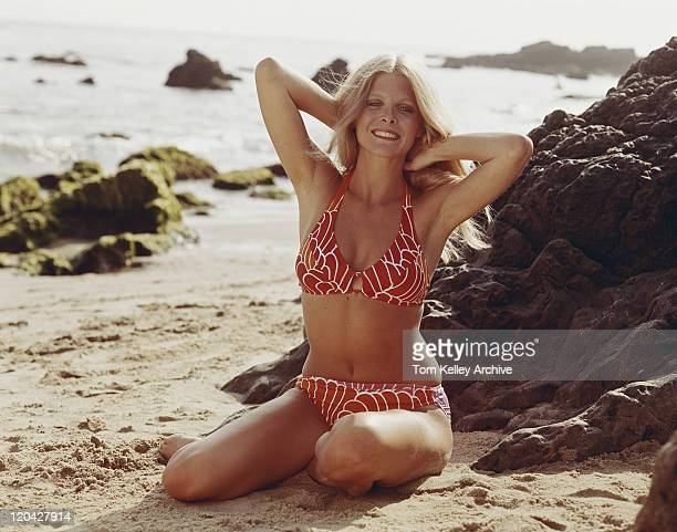 Young woman in bikini sitting on beach, smiling, portrait