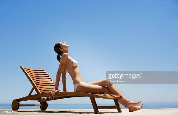 Young woman in bikini sitting on sun lounger