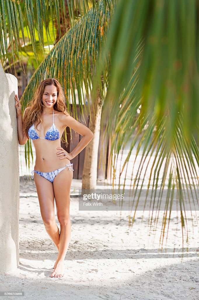 Young woman in bikini standing on beach : Stock-Foto