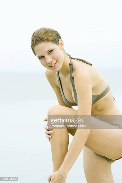 Young woman in bikini standing with one knee up, touching leg, smiling at camera