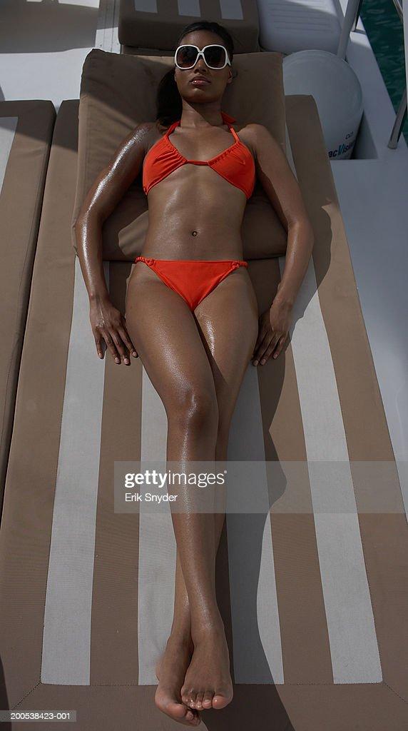 Young woman in bikini sunbathing on yacht : Stock Photo