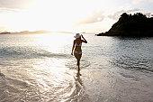 Young woman in bikini walking in ocean, St. John, US Virgin Islands, USA