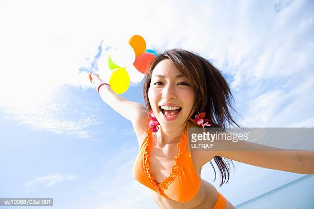 Young woman in bikini with balloons, laughing, portrait