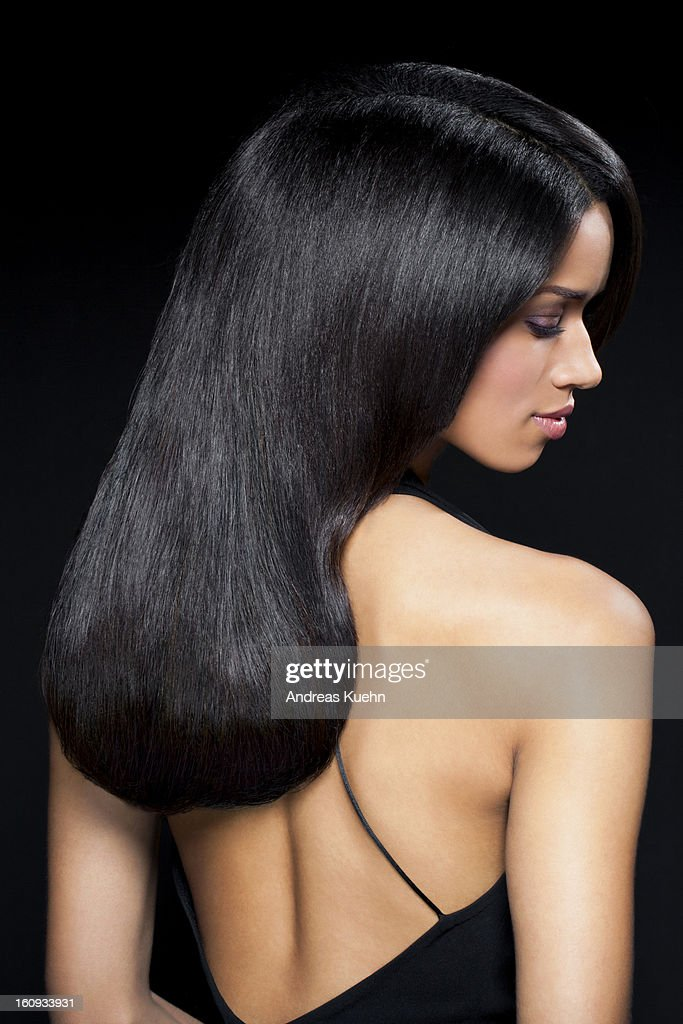 Young woman in black backless dress, profile. : Stock Photo