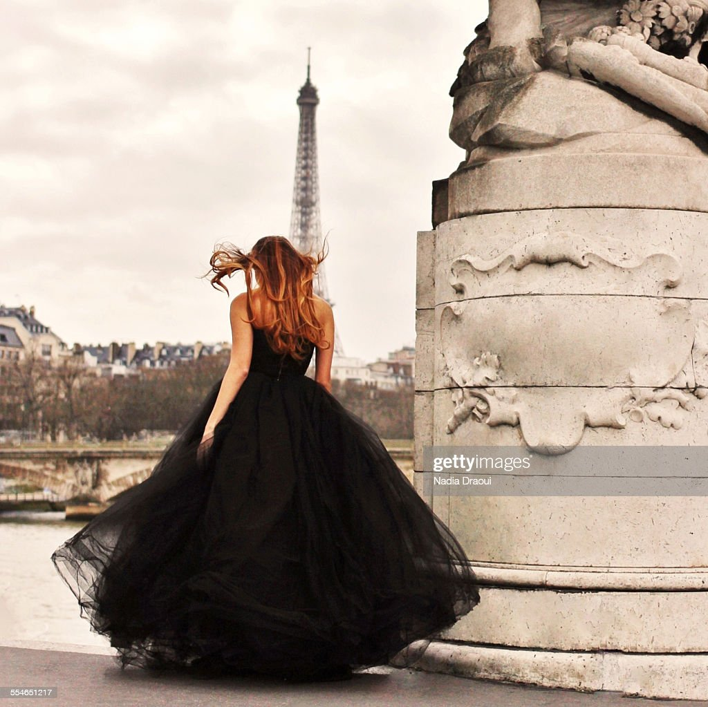 Young woman in black dress looking at Eiffel Tower