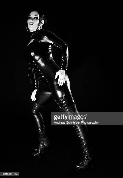 Young woman in black PVC suit and leather boots