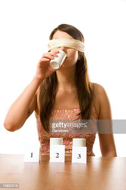 Young woman in blindfold participated in taste test, close-up