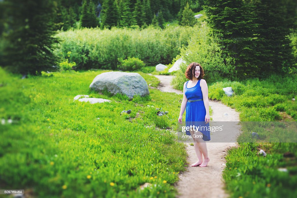 Young woman in blue dress barefoot on path through alpine meadow, looking away