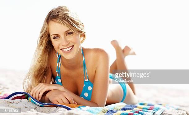 Young woman in blue polka dot bikini on towel at beach