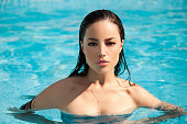 beautiful young woman posing in pool, summer day portrait