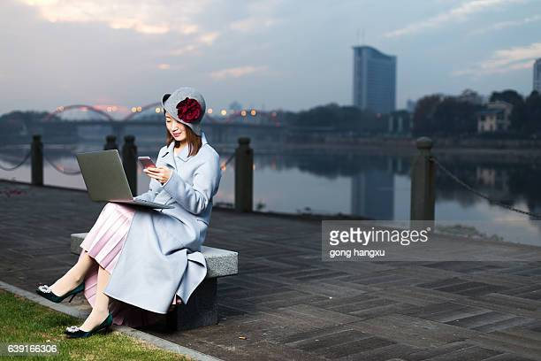 young woman in blue with mobile phone by river