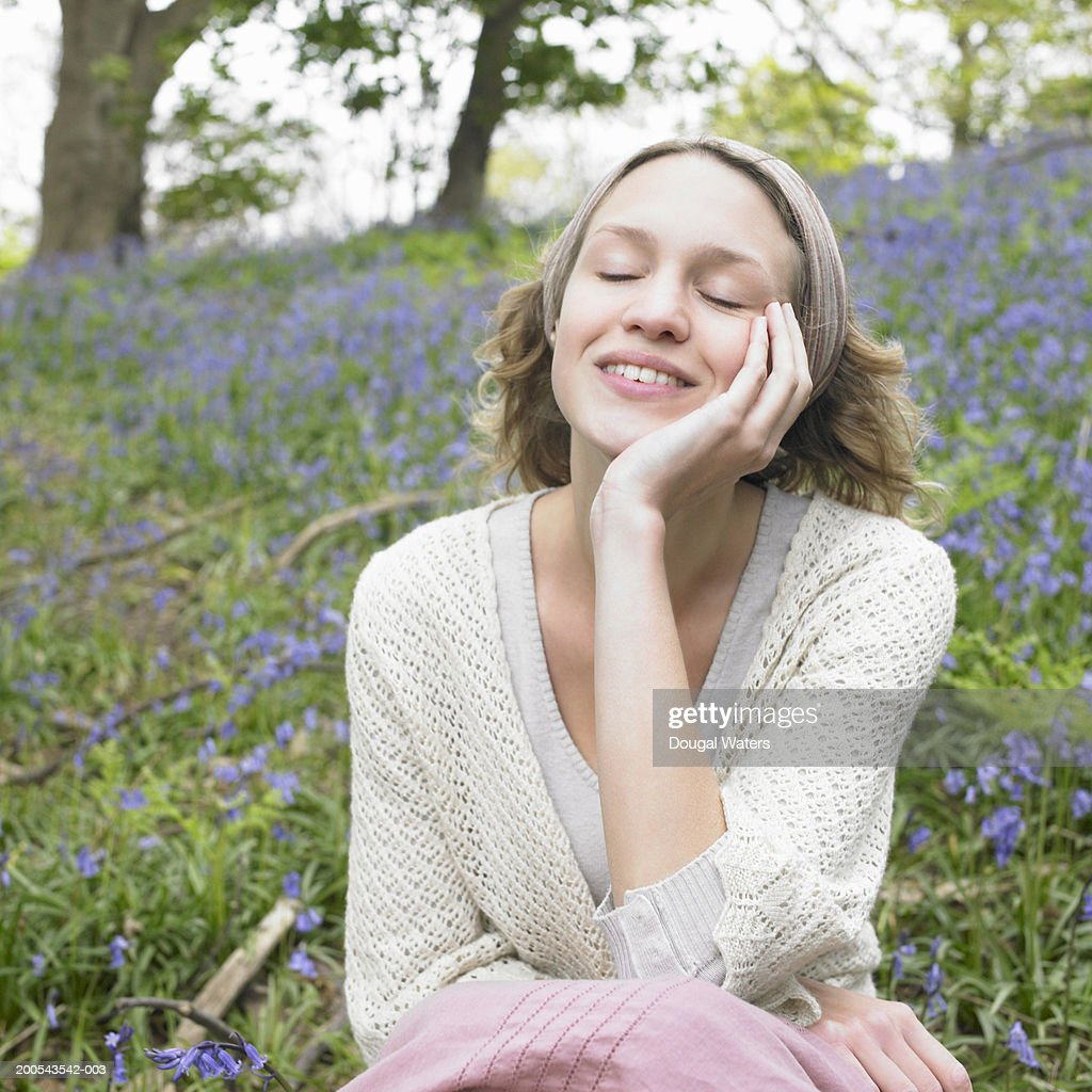 Young woman in bluebell wood, eyes closed