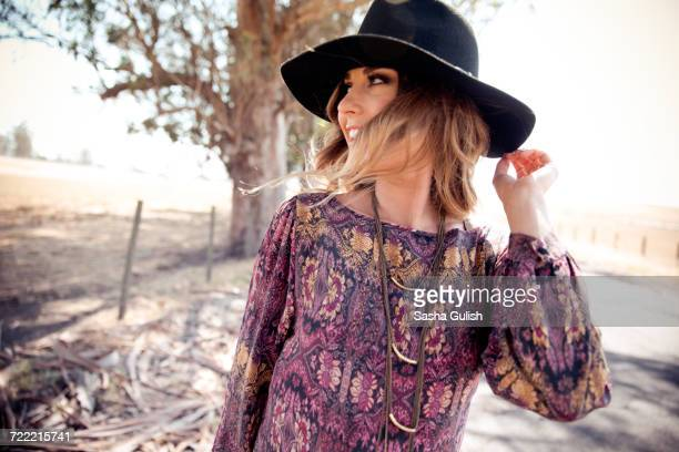 Young woman in boho style and felt hat looking over her shoulder on roadside