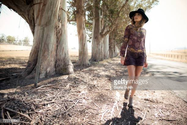Young woman in boho style and felt hat strolling on roadside