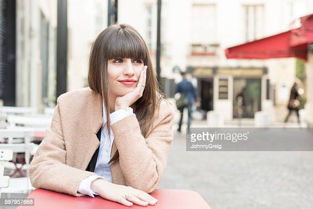Young woman in cafe looking away hand on chin