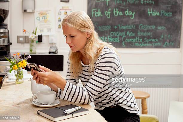 Young woman in cafe reading message mobile phone