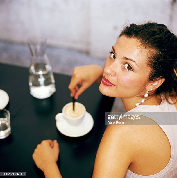 Young woman in cafe stirring drink, portrait, close-up
