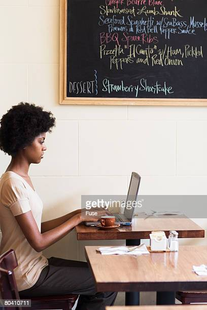 Young Woman in Cafe Using Laptop