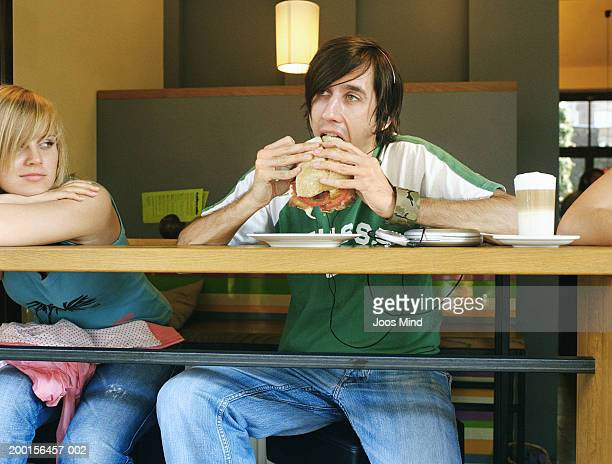 Young woman in cafe watching man bite into sandwich