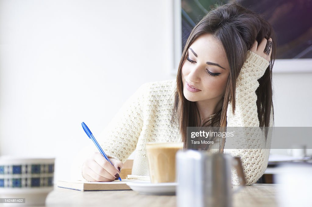 young woman in cafe writing and drinking coffee : Stock Photo
