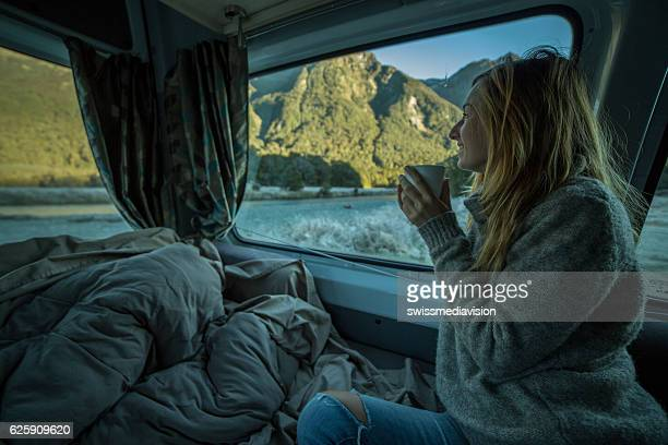 Young woman in camper looks through window, New Zealand
