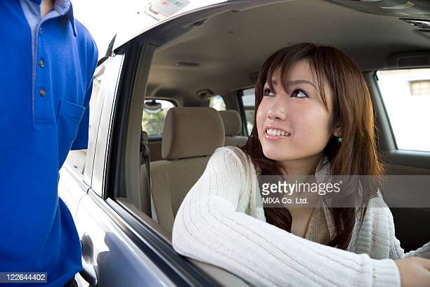 Young woman in car and gas station clerk