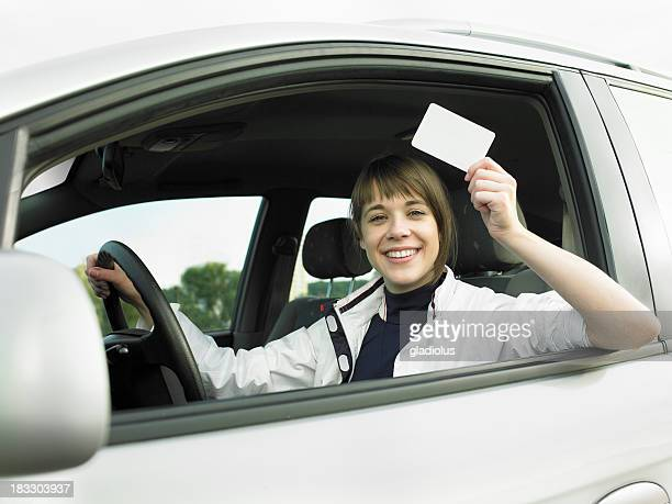 Young woman in car and holding a blank card