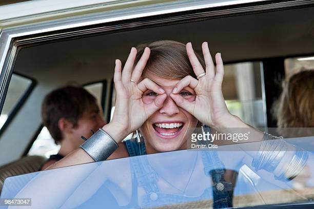 Young woman in car looking through finger circles