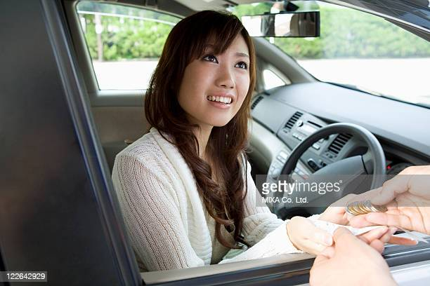 Young woman in car receiving change